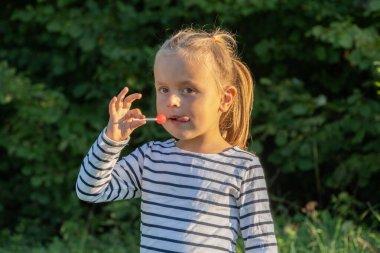 Cute little girl eating lollipop outdoors