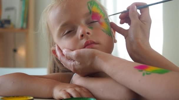 Anya pillangókat rajzol az arcára a kislánya.