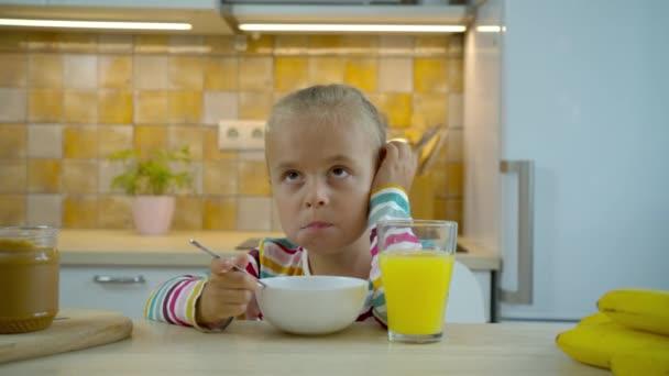 Kleines hungriges Mädchen isst Flocken mit Milch und trinkt Saft