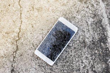 Close up of broken mobile phone drop on cement floor