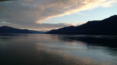 Mountain Filled horizon on the pacific ocean. Inside passage Alaska at sunset with the bright colors shining off clouds