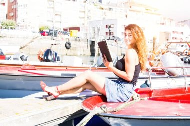 Young woman reading book on a boat