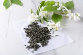 Dry leaves of green tea on the paper and jasmine flowers on the white surface