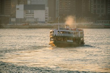 green passenger Ferry in victoria harbour with cityscape background against morining sunrise, services between Kowloon and Hong Kong Island