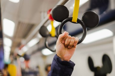 woman holding hand grip in Disney Line MTR inside from Sunny bay to Hong Kong Disneyland resort, landmark for tourist attraction; Hong Kong, China,17 December 2018
