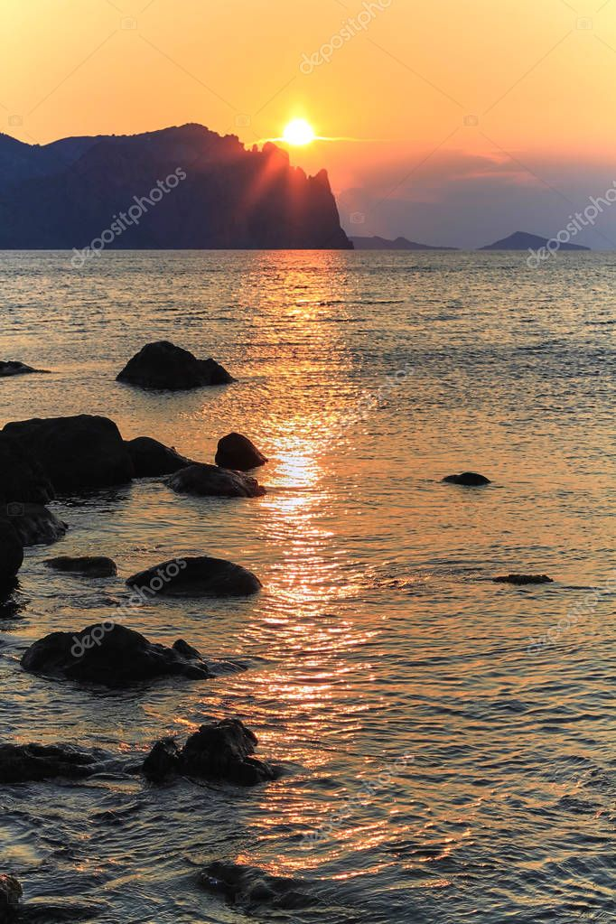 the dawn of the sun, the bright solonets comes out from behind the mountains and the sea glitters and sparkles in different colors