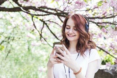 Young woman listening music in earphones in spring blooming garden