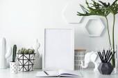 Moderno posto di lavoro bianco con notebook aperto, figure e cornice su sfondo bianco