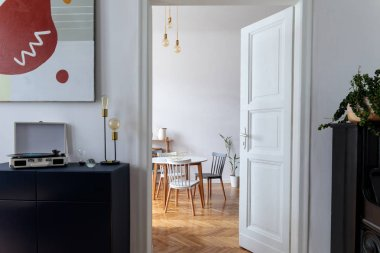 Stylish scandinavian interior of dinning room with modern apartment with design furnitures, white walls, brown wooden parquet and elegant accessories. Cozy home decor.