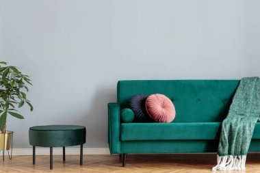 Minimalistic home interior with green velvet design sofa and pouf, tropical plant and elegant blanket and pillows. Copy space for inscription, mock up poster. Brown wooden parquet.