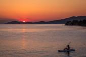 Fotografie Silhouette des jungen Mädchens auf Sup Surf im Wasser bei Sonnenuntergang