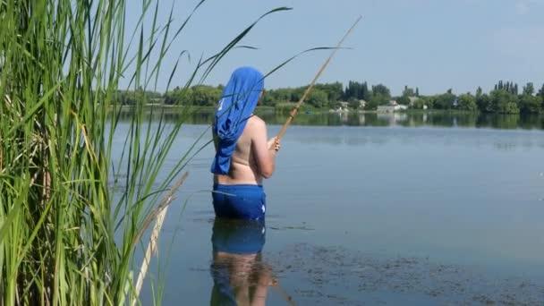 Muž s rybářským prutem na břehu jezera je lov ryb. Rybáři na břehu jezera na slunci.