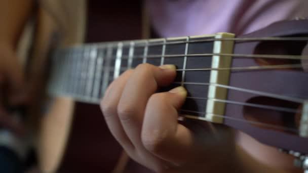 Děti se učí hrát na kytaru. Detailní záběr na kytaru a struny s dětskýma rukama.