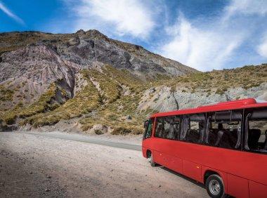 Cajon del Maipo Kanyon - Chile adlı bir yolda kırmızı otobüs