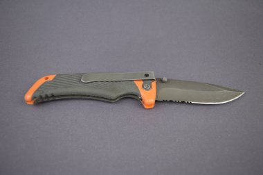 folding pocket knife on a gray background with space for text