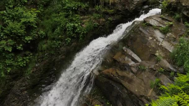 Fallendes Wasser, Felsen und grüne Vegetation