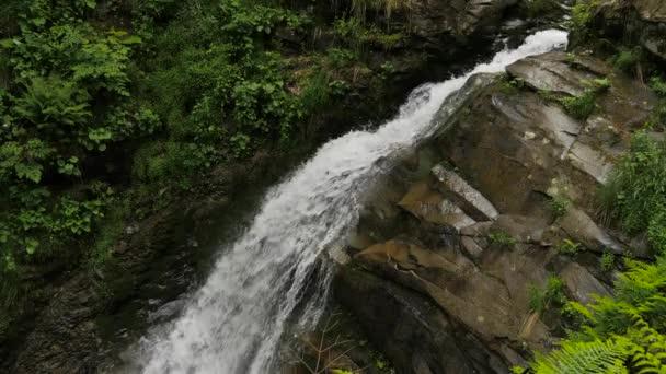 Falling water, rocks and green vegetation