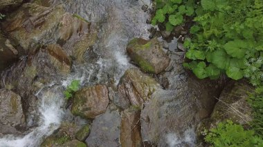 topview of water moveing down at small waterfall, aerial going up shoot
