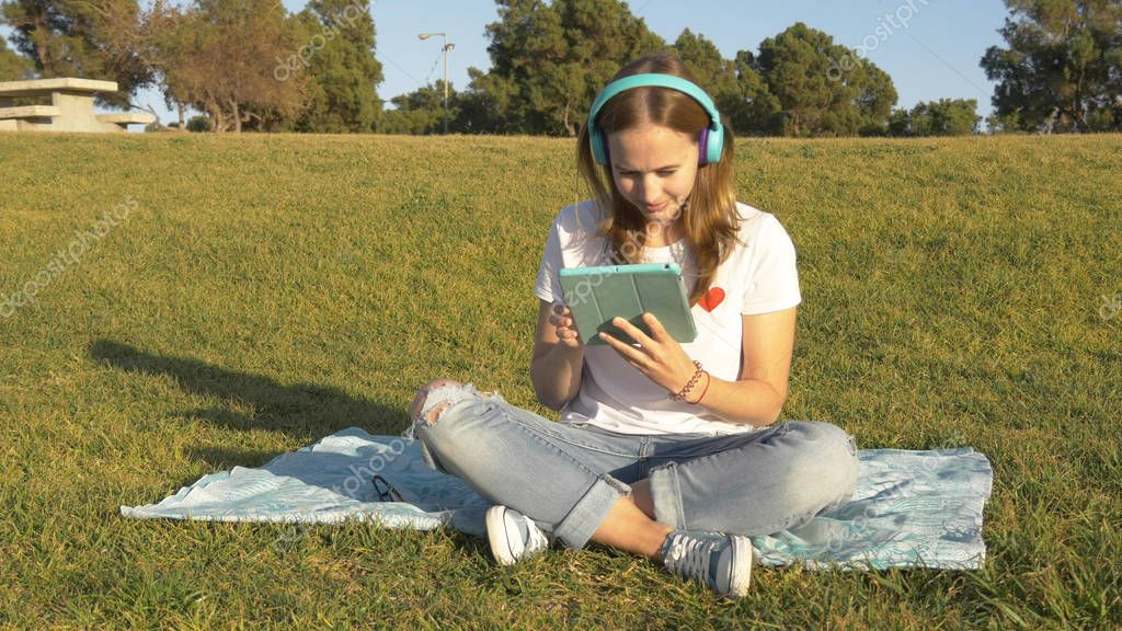 Teenage work with tablet in the park