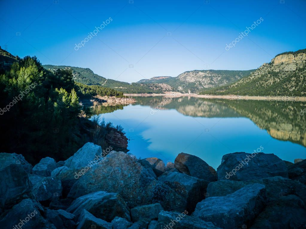 View of Puebla reservoir with mountains in the background and a pine forest