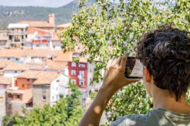 Young man photographing a town