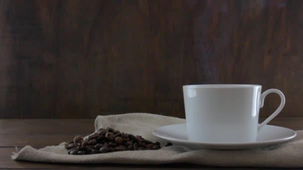 Bílý šálek kávy s párou na dřevěném stole. Kávová zrna. Dřevěné pozadí.