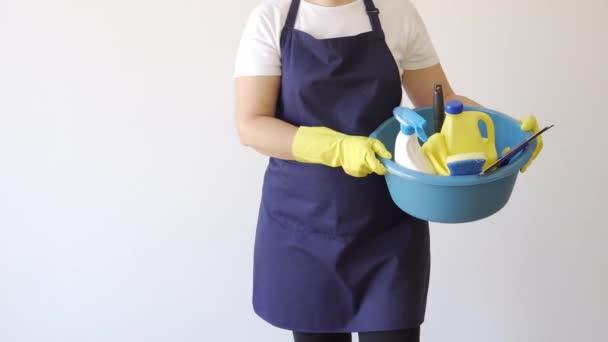 Putzfrau mit Handschuhen trägt verschiedene Reinigungsmittel bei sich. Konzept für Sauberkeit und Desinfektion.