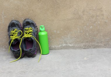 Sports footwear, thermos for water on concrete background