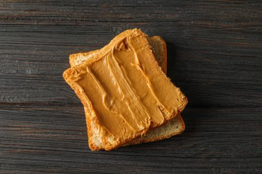 Peanut butter sandwich on wooden background, space for text and