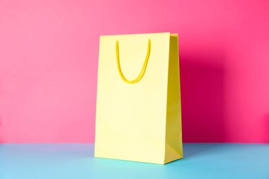 Yellow paper bag on multicolor background, space for text