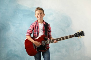 Happy boy with electric guitar on color background, space for te
