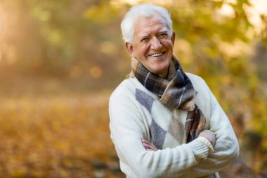 Happy senior man in autumn park