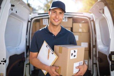 Delivery man standing in front of his van stock vector