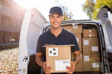 Delivery man standing in front of his van
