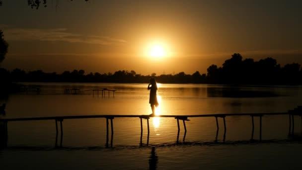 Holčička na dřevěném molu u jezera si odhrnuje vlasy dozadu. Silueta při západu slunce. Koncept letní venkovní rekreace.