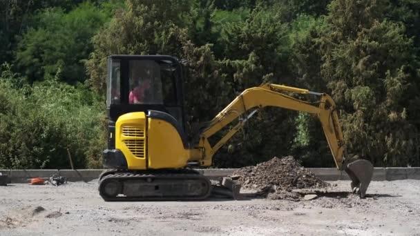 A small yellow excavator digs a trench against a background of green trees.
