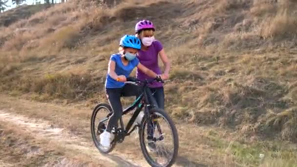 A young mother teaches his daughter to ride a Bicycle in medical masks and a Bicycle helmet in nature near the hill. Protection FROM covid-19 coronavirus infection.