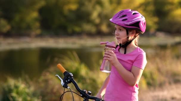 Holčička v cyklistické helmě pije čistou vodu u kola na břehu řeky. Koncept outdoorových sportů.