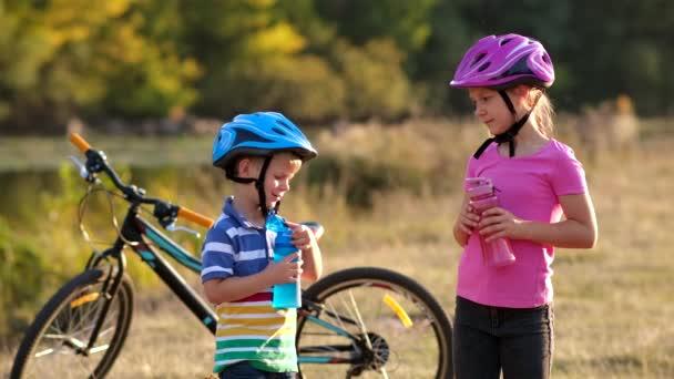 Malá holčička a chlapec v cyklistických helmách pijou čistou vodu u kola na břehu řeky. Koncept outdoorových sportů.