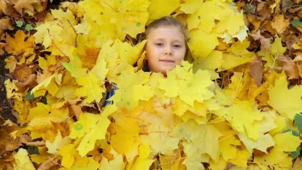 Krásná holčička ležící ve žlutých listech a ukazuje ok znamení s palcem!