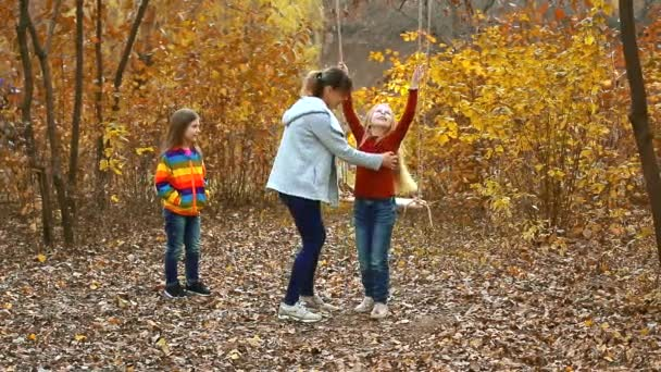 Mom swings children on a rope swing. Happy family in nature in autumn. two beautiful girls are happy and laugh. colorful yellow background.