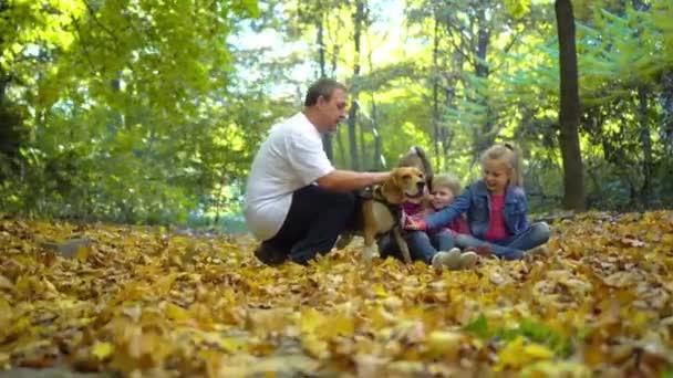 Papa und die Kinder Pat, der Hund der Rasse Beagle. Glückliche Familie in der Natur im Herbst. zwei schöne Mädchen und der Junge sind glücklich und lachen. bunte gelbe Hintergrund.