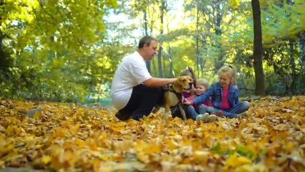 Glückliche Familienspaziergänge im herbstlichen Park mit einem Beagle-Hund. Kinder streicheln Hund.