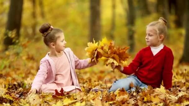 zwei kleine Mädchen sammeln einen Strauß Herbstblätter