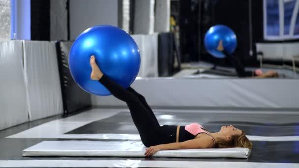 Ein schönes Mädchen macht in der Turnhalle Übungen mit einem großen blauen Gummiball. Das Konzept von Gesundheit und Schönheit.