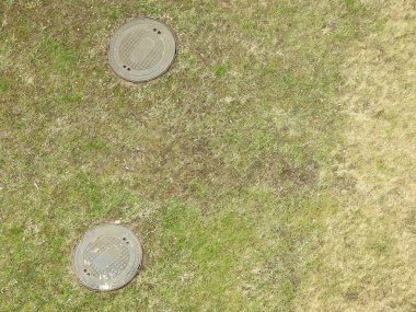 Grass from above with two manholes