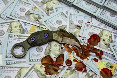 karambit knife on stack bundles of 100 US dollars banknotes bloody