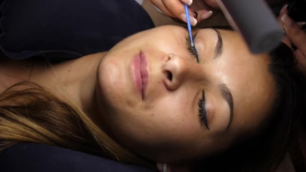 Removal of old lashes. The beautician removes the eyelashes with tweezers. The girl lies on the procedure under the lamp. Eyelash extension. Beautiful young woman on eyelash extension procedure.