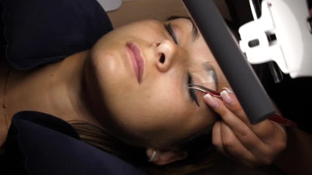 Woman Eye with Long Eyelashes. Eyelash Extension. Lashes, close up, selected focus. Gluing artificial eyelashes with tweezers. A woman lies under a lamp on a cosmetic procedure.