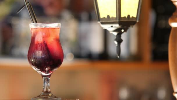 Glaskelch mit schwarzer Johannisbeerlimonade rotiert vor dem Hintergrund der Bar. Eis fällt in ein Glas mit kalter Limonade aus frischen Beeren. Zeitlupe